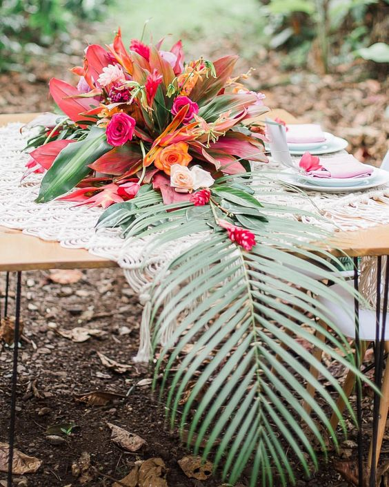 a lush bright floral centerpiece with orange and pink blooms and some large leaves