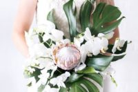 18 a modern tropical bouquet with a creative shape of white orchids, monstera leaves and a single king protea
