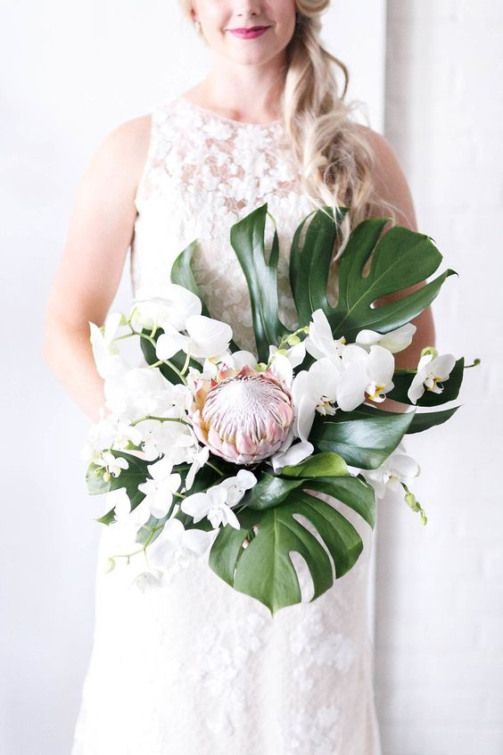 a modern tropical bouquet with a creative shape of white orchids, monstera leaves and a single king protea