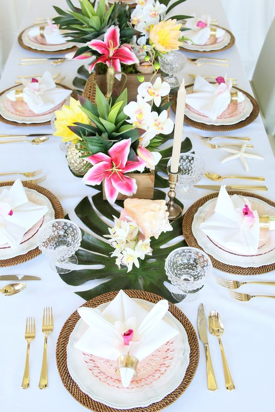 a palm leaf table runner with bold tropical blooms and gilded pineapples for a bold tropical look
