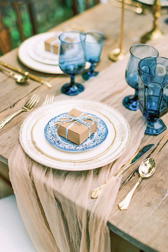 an airy taupe wedding table runner matches the table itself and a box and everything is spruced up with bright blue touches