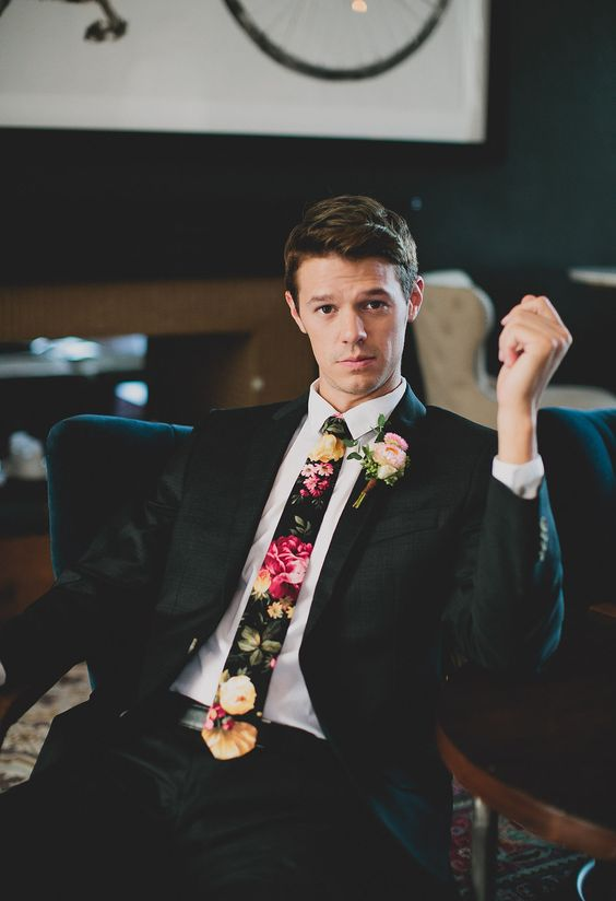 a black suit, a white shirt and a bold floral print tie for a gorgeous groom's look