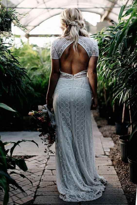 a chic boho lace sheath wedding gown with short sleeves and a cutout back looks very sexy