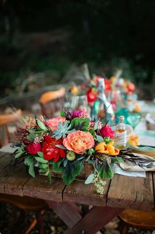 a colorful box centerpiece with orange, red, pink and yellow blooms, herbs and succulents