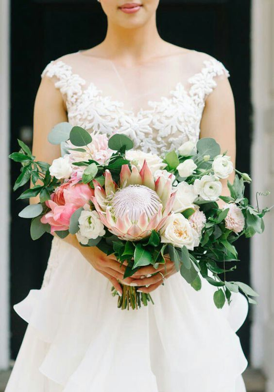 a lush graden wedding bouquet with a king protea, white penoies, pink blooms and much greenery