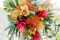 a super bold tropical wedding bouquet with yellow orchids, a cascade and much greenery for a bold and vibrant statement