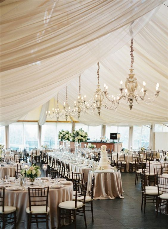 taupe tablecloths and drapings hanging from above plus chandeliers in the same shade for a timelessly elegant look