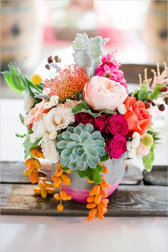 a colorful centerpiece with hot pink, red, orange and blush blooms, succulents and kumquiats