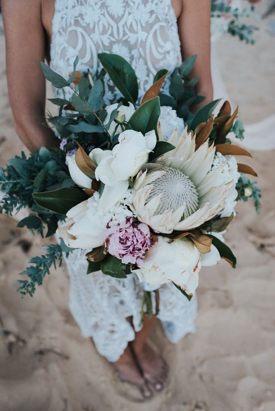 a lush wedding bouquet with a king protea, greenery, blush blooms and magnolia leaves for a tropical bride