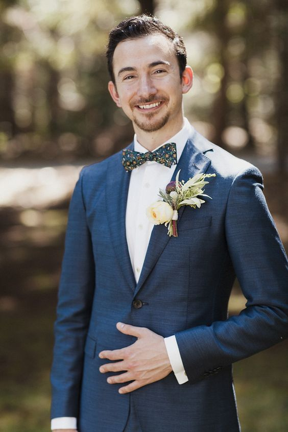 a navy suit, a white shirt and a matching whimsy floral bow tie for a quirky touch