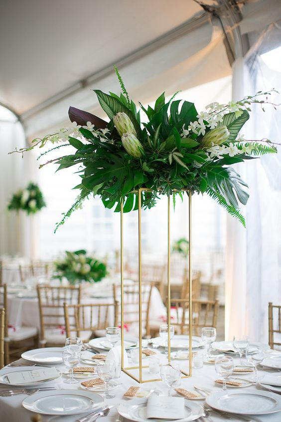 a tall centerpiece on a gilded stand with lush greenery, white blooms and king proteas