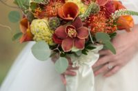 a textural fall bouquet with rust, mauve and orange blooms plus greenery, orchids make it special