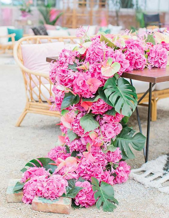 bring paradise to your wedding with a pink floral table runner of palm leaves and tropical blooms cascading down