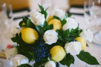 21 a fresh and bright centerpiece with lush greenery, berries, white roses and lemons