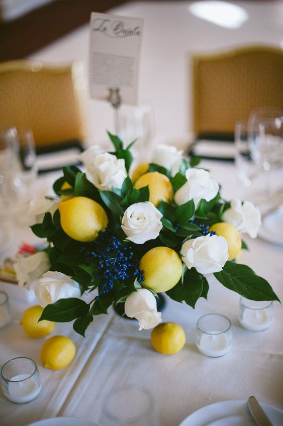 a fresh and bright centerpiece with lush greenery, berries, white roses and lemons