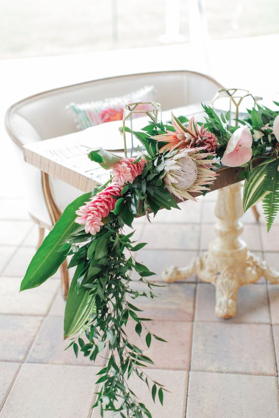 a greenery tropical table runner with king proteas and pink blooms for a sweetheart table