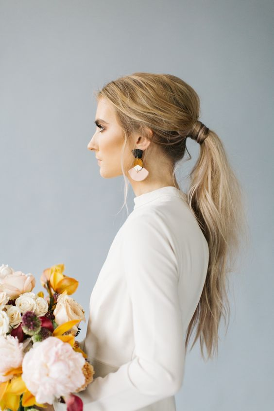 a modern sleek low ponytail with a small bump and textural ends is ideal for a minimalist bride