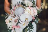 21 a unqiue tropical wedding bouquet with king proteas, blush and mauve roses, greenery and white orchids