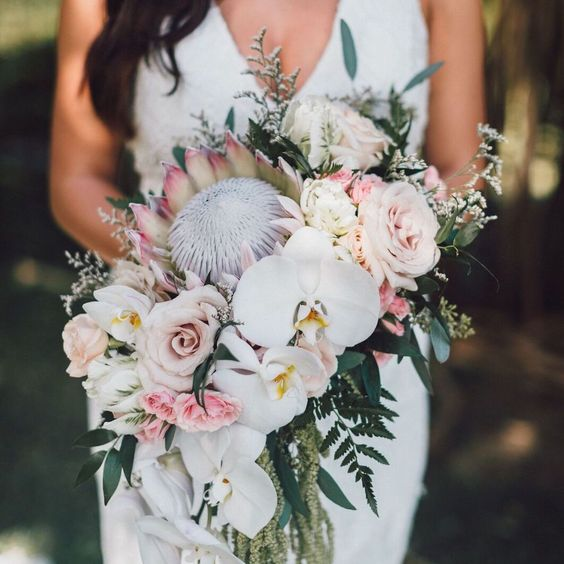 a unqiue tropical wedding bouquet with king proteas, blush and mauve roses, greenery and white orchids