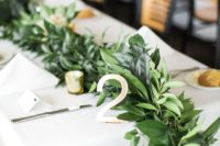 22 a lush and textural greenery table runner with small candles in candle holders is a cute idea