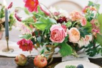 22 a lush floral centerpiece with blush, orange, pink blooms and greenery in a bowl