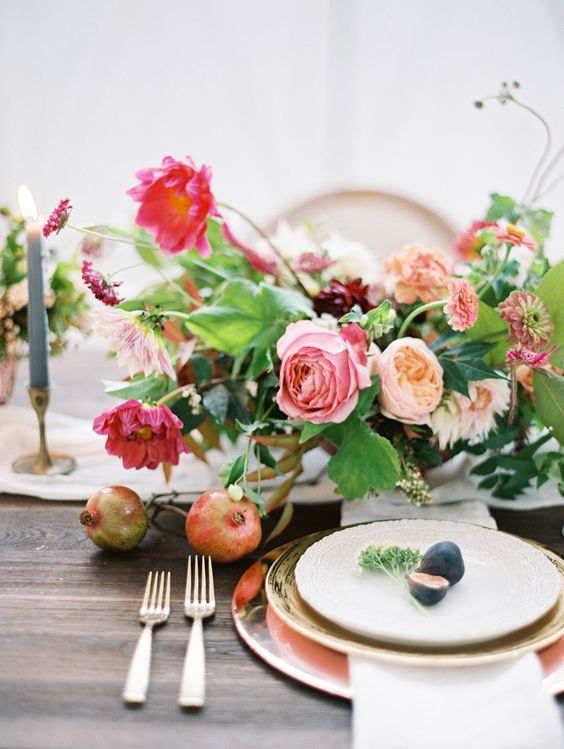a lush floral centerpiece with blush, orange, pink blooms and greenery in a bowl