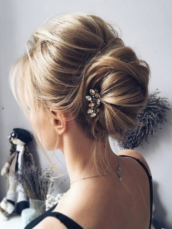 a messy chignon hairstyle with bangs and a rhinestone hairpiece for a modern casual bride