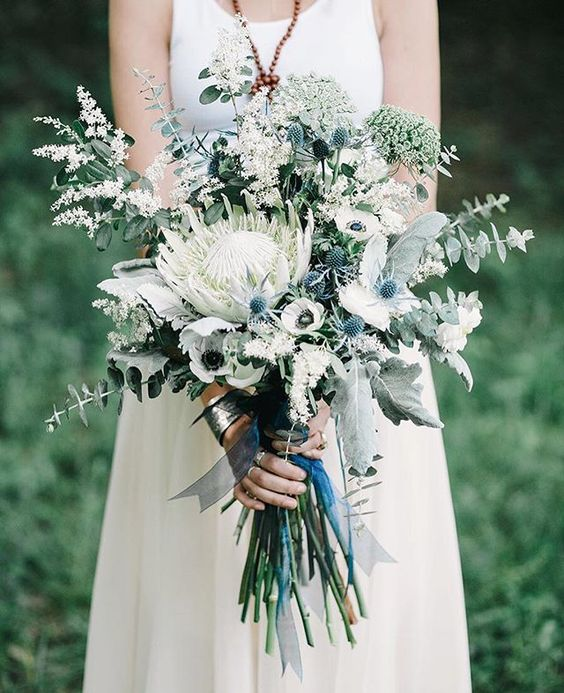 a pale and delicate wedding bouquet with blue thistles, a king protea, white anemones and herbs and eucalyptus