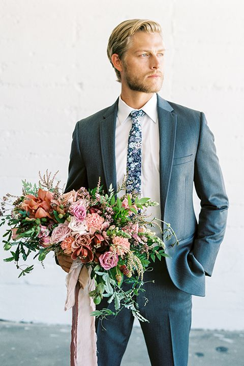 a slate grey suit, a white shirt, a dark floral tie for a fresh summer look