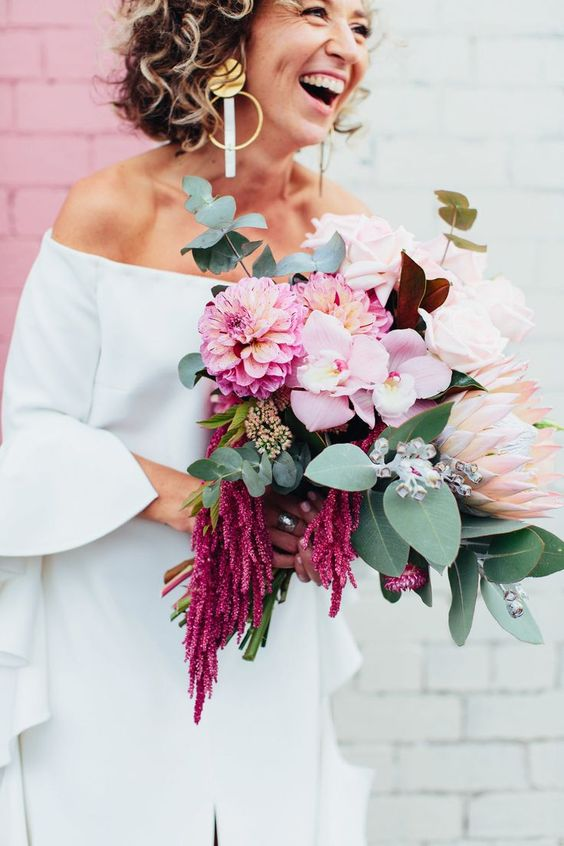 a vibrant bouquet with king proteas, pink orchids, amaranth and fresh greenery for a textural look