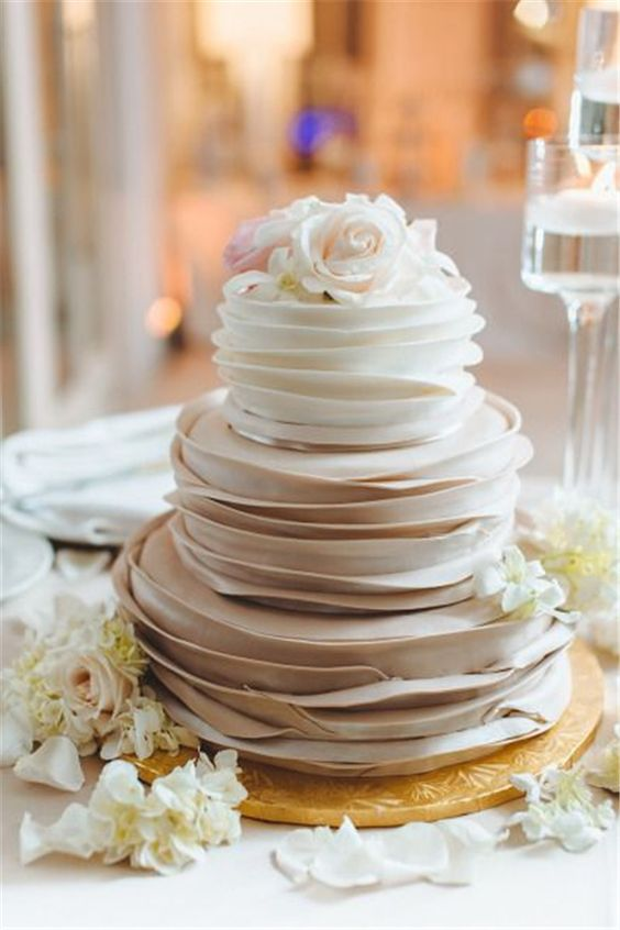 a creative ombre textural wedding cake from white to taupe topped with fresh blooms