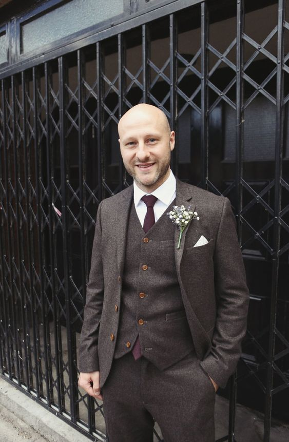 a dark brown three-piece tweed suit, a plum-colored tie, a baby's breath boutonniere for vintage style