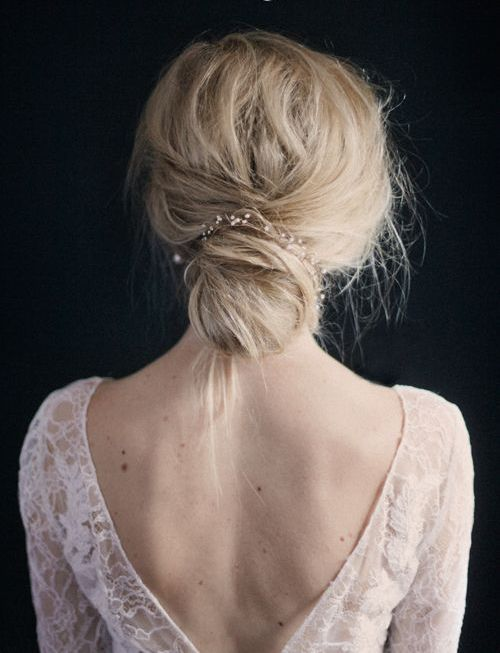 a delicate and romantic low wedidng updo with a cute pearly hair vine and a messy touch