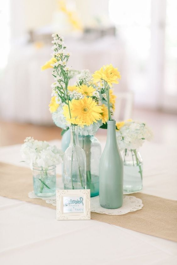 a rustic centerpiece with doilies, clear glass vases and mint bottles plus white and yellow blooms