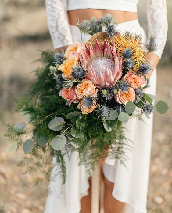 a textural cascading wedding bouquet with a king protea, peachy and yellow blooms, blue thistles and ferns and eucalyptus