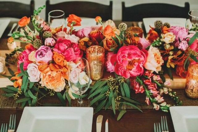 a very colorful and vibrant blooming table runner in pink, orange, blush and yellow with some greenery touches