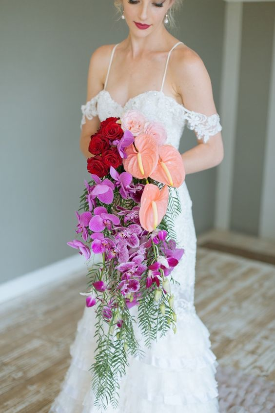 a vibrant cascading wedding bouquet with red roses, pechy callas and hot pink orchids for a bold statement