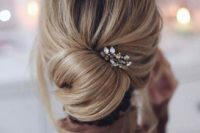 24  a casual and messy low twisted chignon hairstyle with some waves down and a chic rhinestone hairpiece