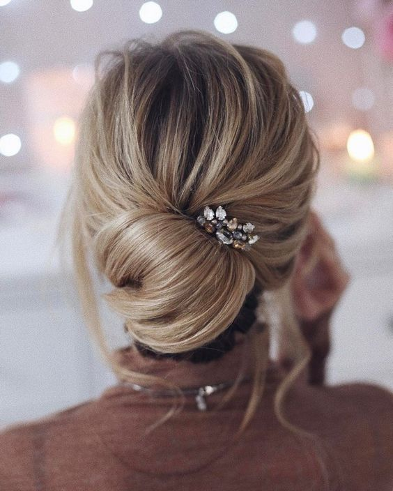 a casual and messy low twisted chignon hairstyle with some waves down and a chic rhinestone hairpiece
