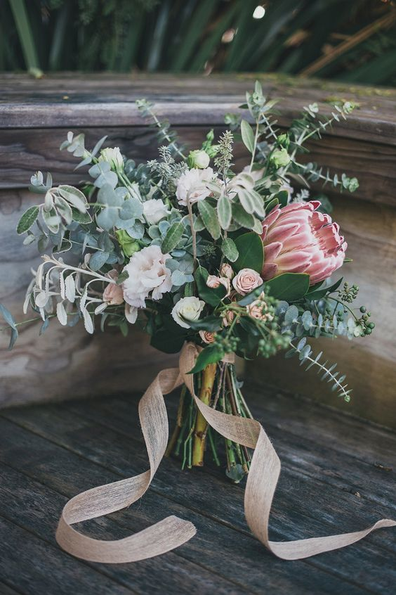 a cute wedding bouquet with eucalyptus, blush garden roses and thistles plus blush ribbons