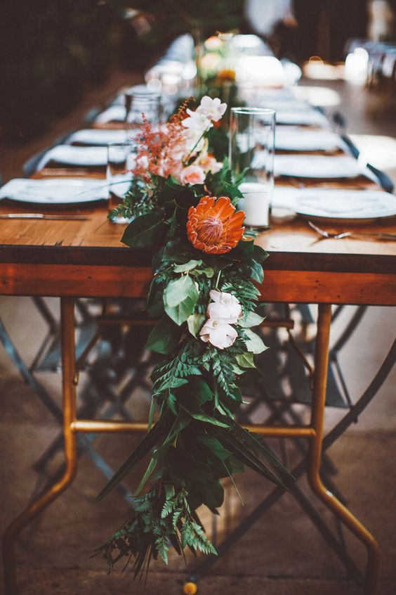 a lush organic table runner of greenery, blush blooms and king proteas that look very tropical-like