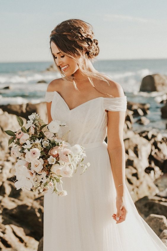 a simple off the shoulder V-neckline A-line wedding dress for a coastal bride