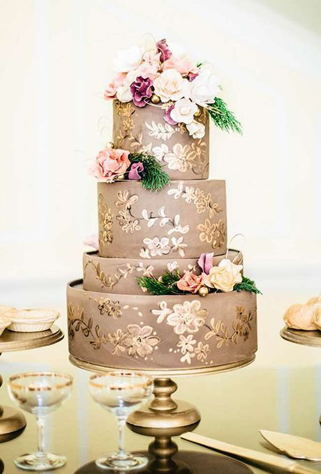 a taupe wedding cake with gold touches and bright fresh blooms and greenery for a refined look