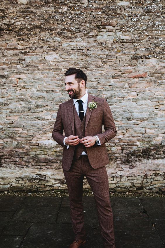 a rich brown three-piece tweed suit with a black tie, brown shoes for a fall wedding