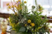 25 a summer woodland centerpiece with ferns, berries, billy balls, yellow flowers and various greenery