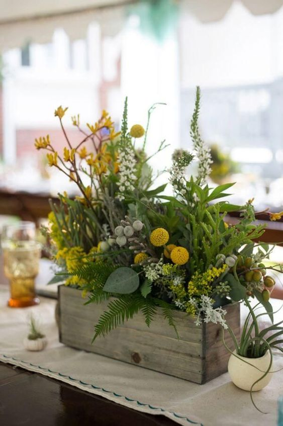 a summer woodland centerpiece with ferns, berries, billy balls, yellow flowers and various greenery