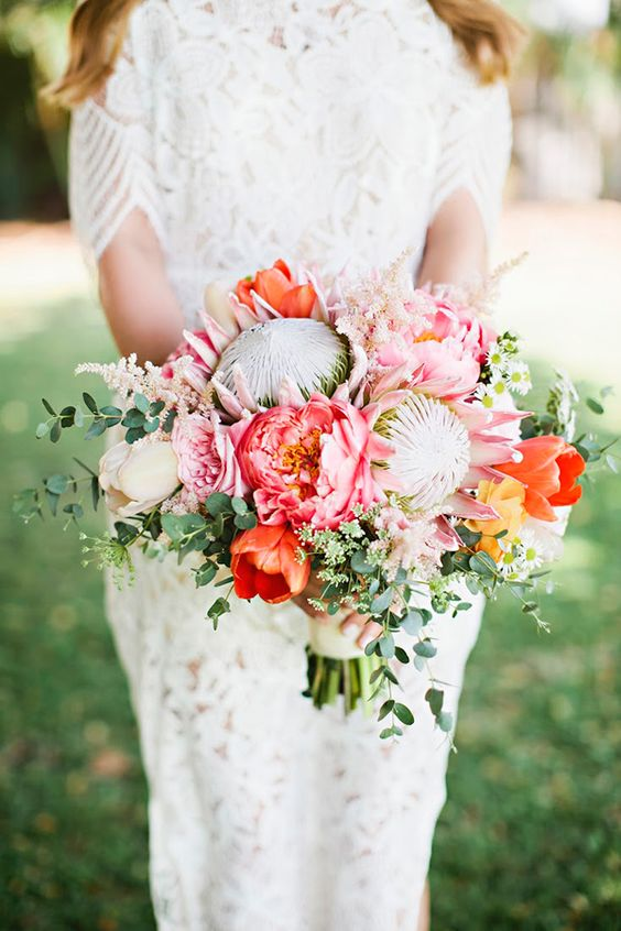 a vibrant wedding bouquet with king proteas, pink and orange blooms and greenery for a summer wedding