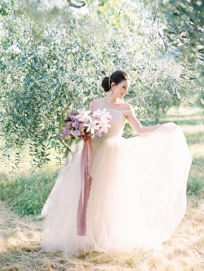 an ethereal off the shoulder blush wedding dress with an A-line silhouette