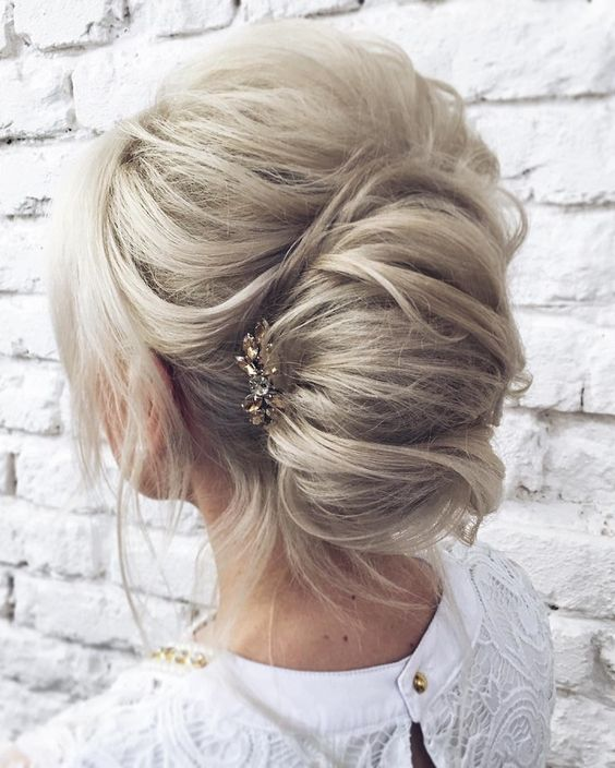 a messy casual chignon hairstyle with some waves down and a bump on top plus a rhinestone hairpiece