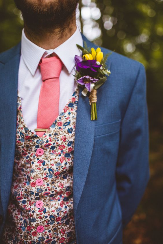 a slate blue suit, a colorful floral print vest, a matching pink tie for a fashionable groom's outfit